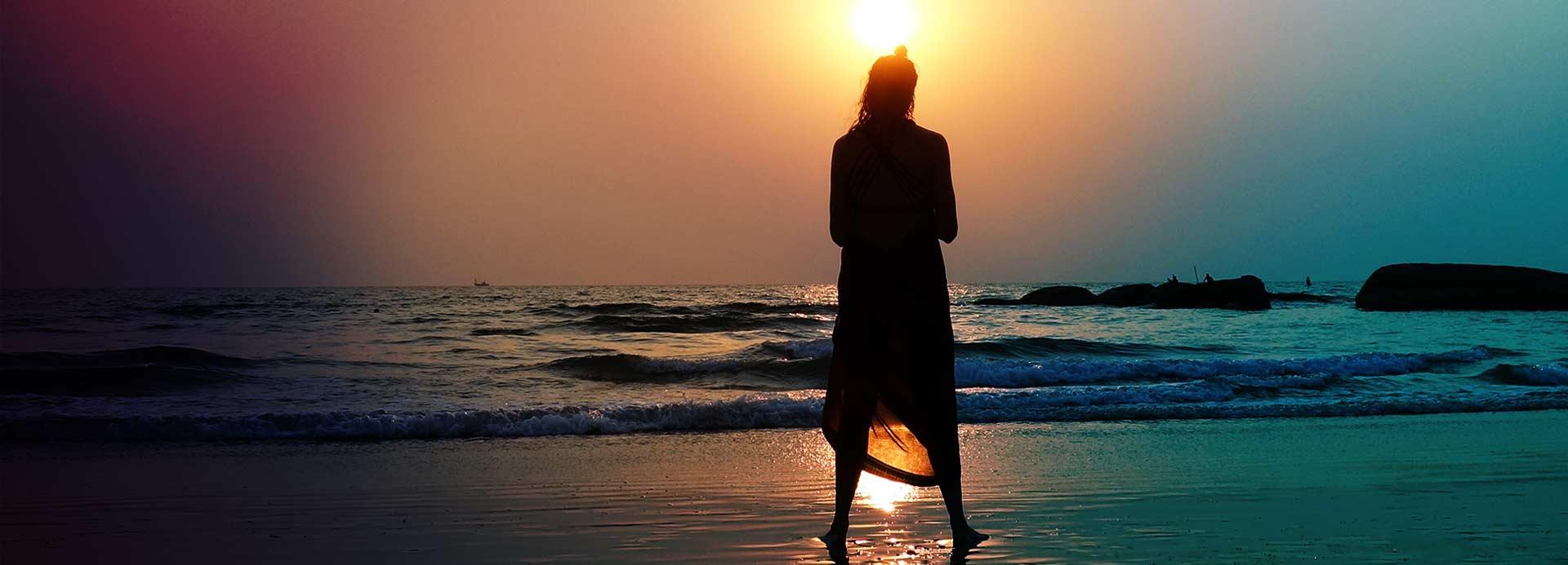 Silhouette einer Frau am Strand über deren Kopf die Sonne hell scheint